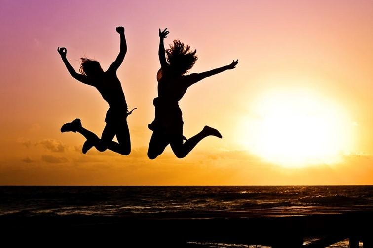 2 personer som hopper av glede i solnedgangen