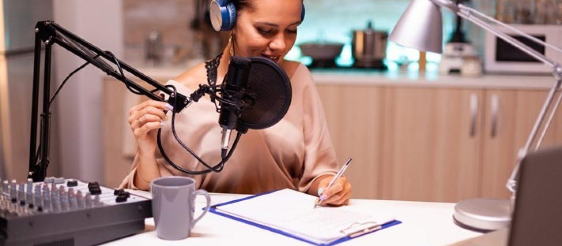 Dame som sitter å skriver på en blokk i studio.